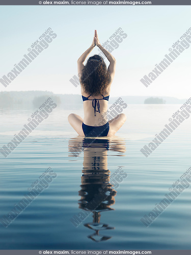 Artistic photo of a woman meditating on a platform in calm water on a misty lake in early morning during sunrise. Yoga meditation. Rear view. Muskoka, Ontario, Canada.