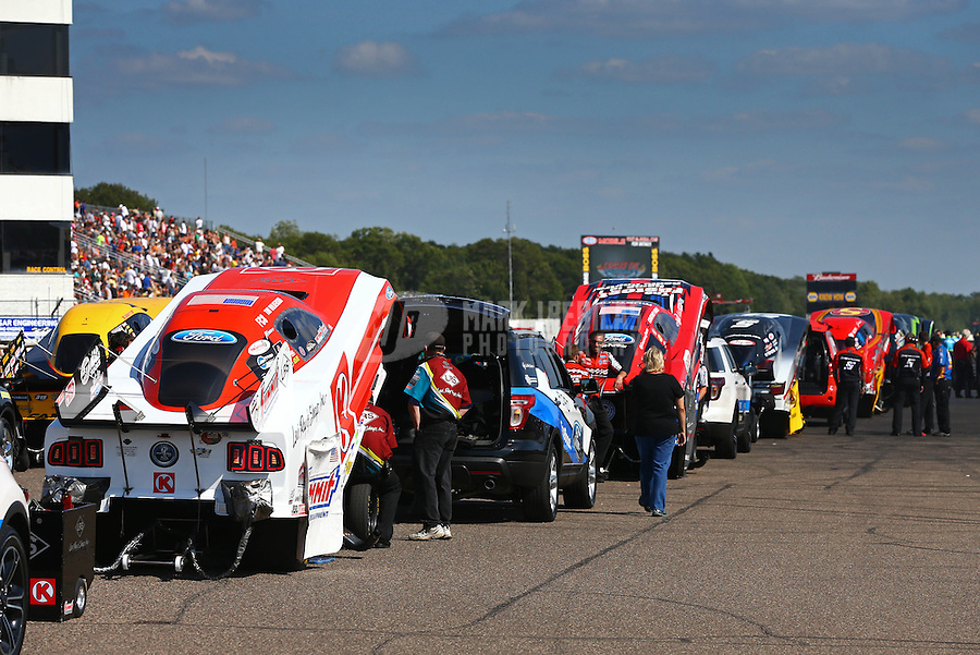 Aug. 17, 2013; Brainerd, MN, USA: The car of NHRA funny car driver Tim Wilkerson (left) waits in line in the staging lanes during qualifying for the Lucas Oil Nationals at Brainerd International Raceway. Mandatory Credit: Mark J. Rebilas-