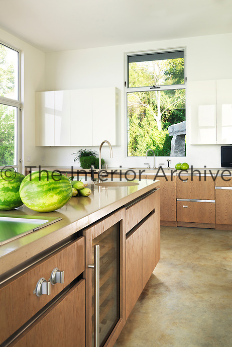 The light, modern kitchen has cast concrete work surfaces and wooden units
