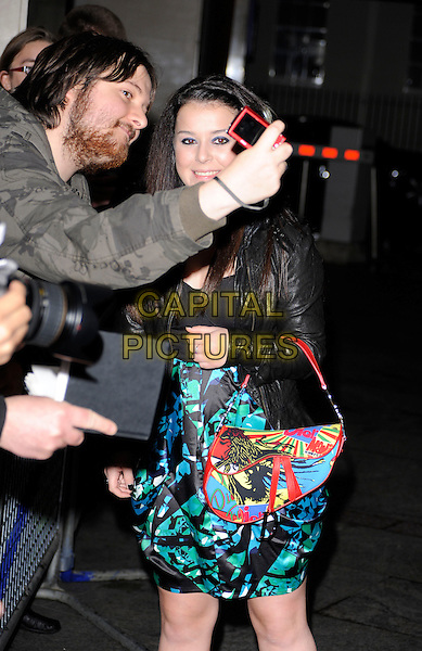 DANI HARMER.At the EA British Academy Children's Awards, Hilton Park Lane, London, England, UK, 29th November 2009..BAFTA BAFTAs half length fan camera taking photo picture red Dior saddle bag print green blue pattern leather black jacket .CAP/CAN.©Can Nguyen/Capital Pictures