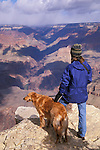 Hiker and dog looking into the Grand Canyon from the south rim, Grand Canyon National Park, Arizona