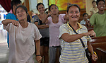 Iris Dizono (right) and Yolanda Vawhi sing enthusiastically during worship at Knox United Methodist Church in Manila, Philippines. The service is part of a weekday program where the church opens up to poor people in the neighborhood, offering showers, food, fellowship, and an opportunity to worship together.