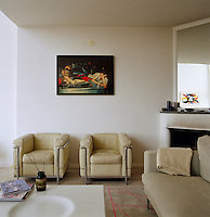 A pair of Le Corbusier leather armchairs underneath a photograph by Nan Golding in the living room