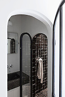 A glimpse into the shower room reveals a wash basin in Belgian stone and a shower cubicle lined with Moroccan tiles