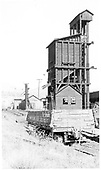 D&amp;RGW drop-bottom gondola #718 with Durango coaling tower and sand house in background.<br /> D&amp;RGW  Durango, CO