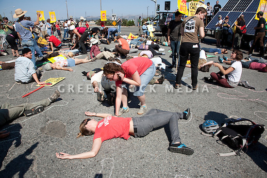 August 15, 2009. Protesters stage a 'die-in' by having people lie down on the ground and have their outlines traced with chalk. About two hundred people participated in a rally, march, and demonstration protesting Chevron's Richmond oil refinery renovation and expansion project. The event was organized by Mobilization for Climate Justice-West, a coalition of over thirty organizations, working to bring awareness to the refinery issue as well as the United Nations Climate Change Conference taking place in December in Copenhagen. Event organizers claim that the Richmond refinery project will allow the facility to refine heavier and dirtier crude that will result in more air pollution, greenhouse gas (GHGs) emissions, and health risks. A court ruling recently put the refinery project on hold saying that further environmental impact reporting was needed. Many protesters were also concerned about the environmental and human health impacts of oil company projects outside the United States. Richmond, California, USA