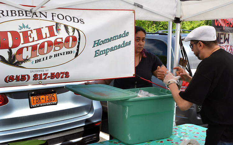 Market Manager, Christine Moss, helping, Bobby Bruno, Owner-Chef of Cafe Deli-cioso, at his booth, where he gave a cooking demonstration, at the Opening Day of the 2017 Saugerties Farmer's Market on Saturday, May 27, 2017. Photo by Jim Peppler. Copyright/Jim Peppler-2017.