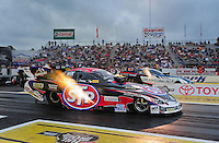 Jun. 1, 2012; Englishtown, NJ, USA: NHRA funny car driver Tony Pedregon (near lane) races alongside Tim Wilkerson during qualifying for the Supernationals at Raceway Park. Mandatory Credit: Mark J. Rebilas-
