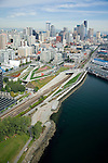Aerial photo looking south along the Seattle waterfront with the Sculpture Park in the center and downtown back right.  The BNSF railroad train tracks that supply the Port of Seattle were a major obstacle to work around.  More than 200,000 yards of fill were added to raise the site of the park above the existing thoroughfares.