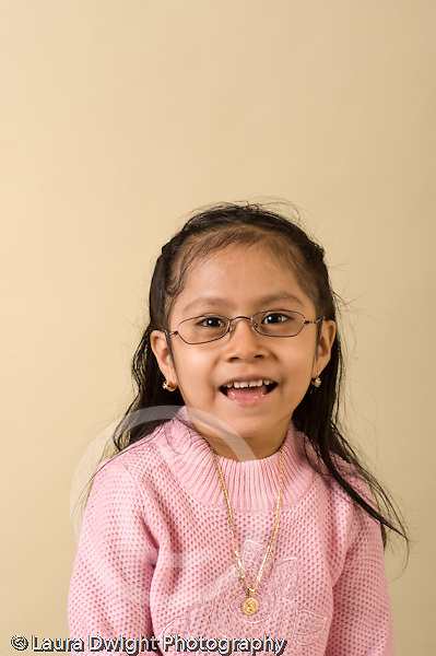 closeup headshot portrait of girl age 4 or 5 vertical wearing glasses