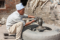 Bhaktapur, Nepal.  Potter Using a Potter's Wheel in Potters' Square.