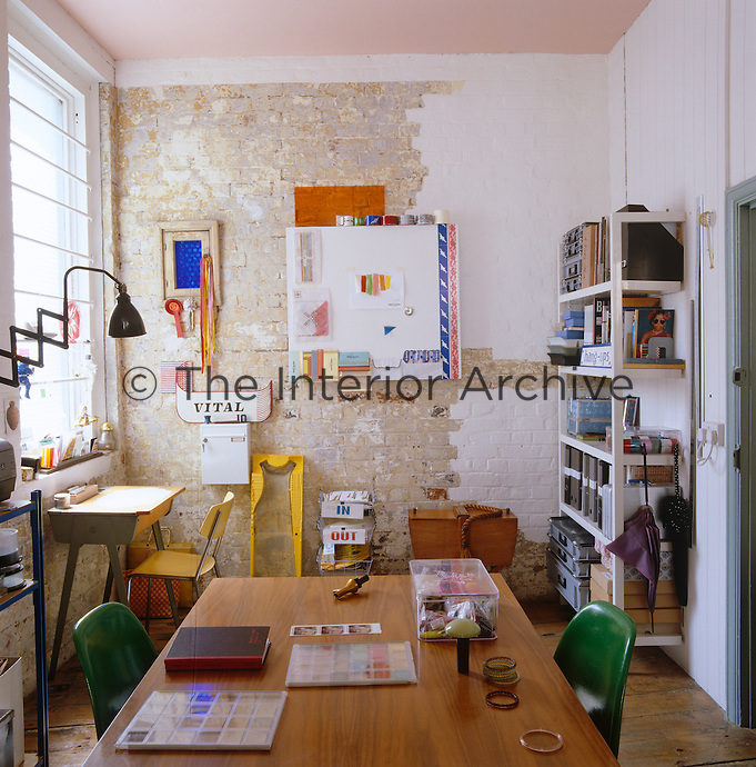 The home office/studio with an old-fashioned school desk and a half-painted brick wall