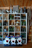 A collection of marine bric-a-brac and antiques collected over the years is displayed on a set of open shelves in the living area