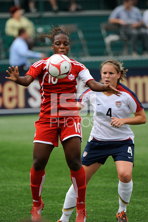 Jodi-Ann Robinson (10) of Canada (CAN) plays the ball as Cat Whitehill (4) of the United States (USA) watches. The United States (USA) Women's National Team defeated Canada (CAN) 1-0 during an international friendly at Marina Auto Stadium in Rochester, NY, on July 19, 2009.