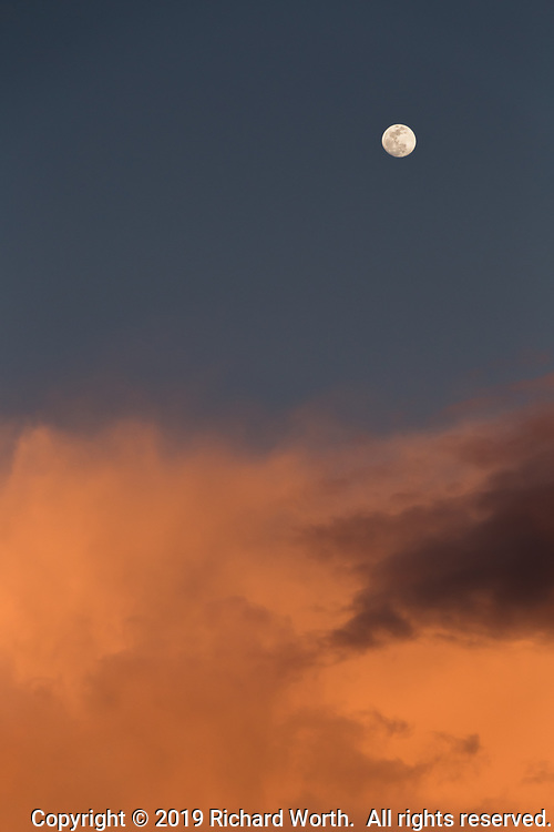 Two days away from the February Full Moon, the waxing gibbous moon floats over glowing sunset clouds near San Francisco Bay.