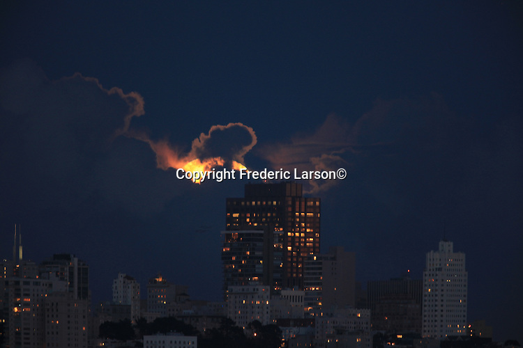 The full moon slowly appears out of the clouds over the bank of America building as seen from Fort Baker Pier in Sausalito California.