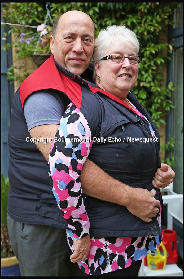 BNPS.co.uk (01202 558833)<br /> Pic: SamSheldon/BNPS<br /> <br /> Geoff Divall and his wife Dot manage to fit in to one of Geoff's old coats.<br /> <br /> A portly plumber who went on a diet after getting stuck under floor boards on a job has lost a massive 11 stone in 12 month.<br /> <br /> Despite being a vegetarian Geoff Divall, 52, tipped the scales at 28 stone and was as wide as he was tall after spending years gorging on cheese and chocolate.<br /> <br /> His obese size led to him having type 2 diabetes and suffering from heart problems. His XXXXXXL size also forced him to have to travel to America once a year to buy big clothes.