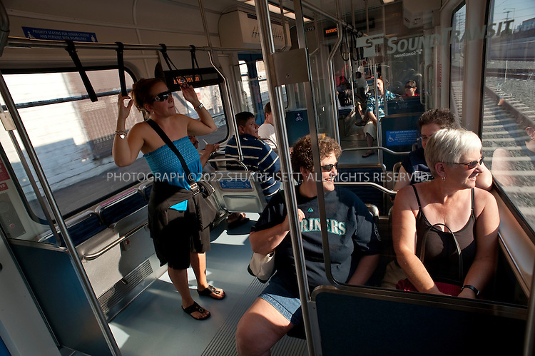"""7/28/2009--Seattle, WA, USA..Seattle Mariners baseball fans take the Sound Transit Link train into Seattle. (no names: got off train) for a game...The Sound Transit Link Light Rail opened in Seattle on July 20th 2009, after decades of planning and political wrangling. Construction of the city's new mass transit system took five years and cost $2.3 billion. By the end of the 2009 Sound Transit says light rail will reach Sea-Tac Airport; the train currently runs 14 miloes from the downtown Westlake station to Tukwila, south of Seattle, with extensions planned to run north and east out of the city.The first efforts to build modern rail transit in the Seattle area began about 50 years ago. A comprehensive plan was defeated by voters three times (1968, 1970, 1995), and then a shortened, """"starter"""" system was passed in 1996. ..©2009 Stuart Isett. All rights reserved."""