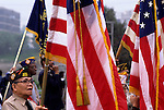 Veterans Day parade along the Seattle waterfront with an Asian vet holding the American Flag getting ready to join the parade
