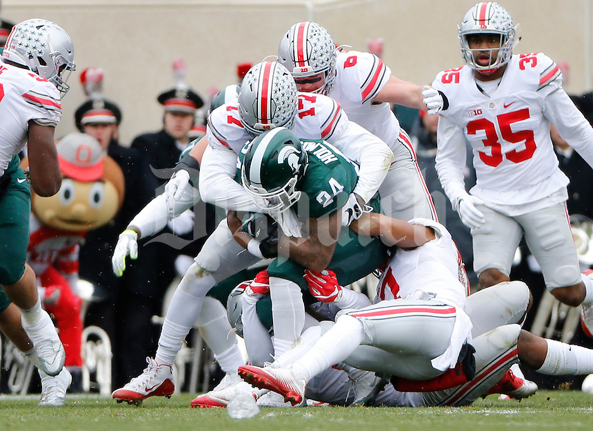 Ohio State Buckeyes linebacker Jerome Baker (17) and safety Damon Webb (7) tackle Michigan State Spartans running back Gerald Holmes (24) during the first quarter of the NCAA football game at Spartan Stadium in East Lansing, Mich. on Nov. 19, 2016. (Adam Cairns / The Columbus Dispatch)