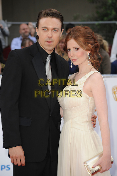 GUEST & AMY NUTTALL .Attending the Philips British Academy Television Awards, Grosvenor house Hotel, Park Lane, London, England, UK, May 22nd 2011..arrivals TV Baftas Bafta half length black suit  one shoulder  cream white dress smiling .CAP/WIZ.© Wizard/Capital Pictures.