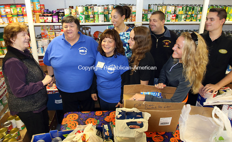 TORRINGTON CT. 15 November 2016-111816SV02-From left, Peggy Hotchkiss of the Torrington Chapter of UNICO gives a $425 donation to Maureen Hubert, Executive Director of the Friendly Hands Food Bank, and Tina Hasapis of the food bank at the food bank in Torrington Friday. Members of the Oliver Wolcott Tech. Aces Club, the youth chapter of UNICO, at right, also dropped off a $100 check to the food bank. The food bank gives out 190 baskets including turkeys for Thanksgiving the donations will help with that cause. <br /> Steven Valenti Republican-American