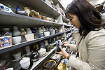 A woman looks at items of pottery on display at Kappabashi Maeda, a kitchenware store in Kappabashi district, Tokyo, Japan on Oct. 13 2010. Often called Tokyo's Kitchen Town, stores in Kappabashi still mainly caters to professionals in the catering industry, though is becoming increasingly popular with foreigners hunting for unique souvenirs. Photographer: Robert Gilhooly