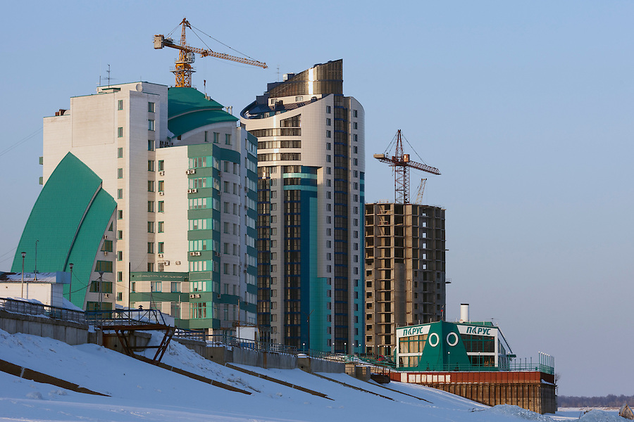Barnaul, Altai Region, Siberia, Russia, 24/02/2011..New apartment and office complex under construction on the banks of the frozen River Ob.