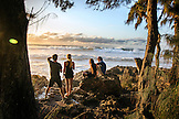HAWAII, Oahu, North Shore, bystanders watch a big swell roll in at sunset at Pupukea Beach Park on the North Shore