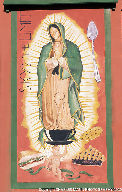 A mural on the side of a coffee and pastry shop in Las Cruces, New Mexico, depicts the Virgin of Guadalupe emerging from a coffee cup, supported by an infant and surrounded by delicious food and  a spoon