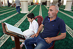 A Palestinian man and his boy read the Koran, Islam's holiest book, at a mosque in Gaza City on the Muslim holy month of Ramadan, on May 20, 2018. Ramadan is sacred to Muslims because it is during that month that tradition says the Koran was revealed to the Prophet Mohammed. The fast is one of the five main religious obligations under Islam. Muslims around the world will mark the month, during which believers abstain from eating, drinking, smoking and having sex from dawn until sunset. Photo by Mahmoud Ajour
