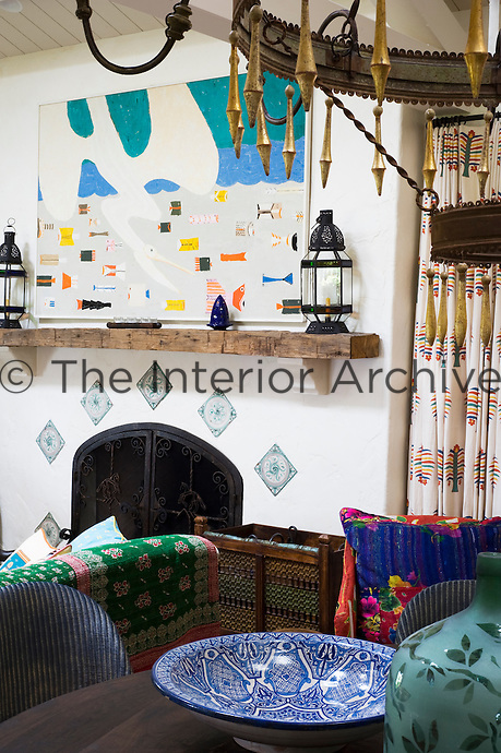 Looking over the dining table towards a simple wooden mantelpiece over the grated fireplace