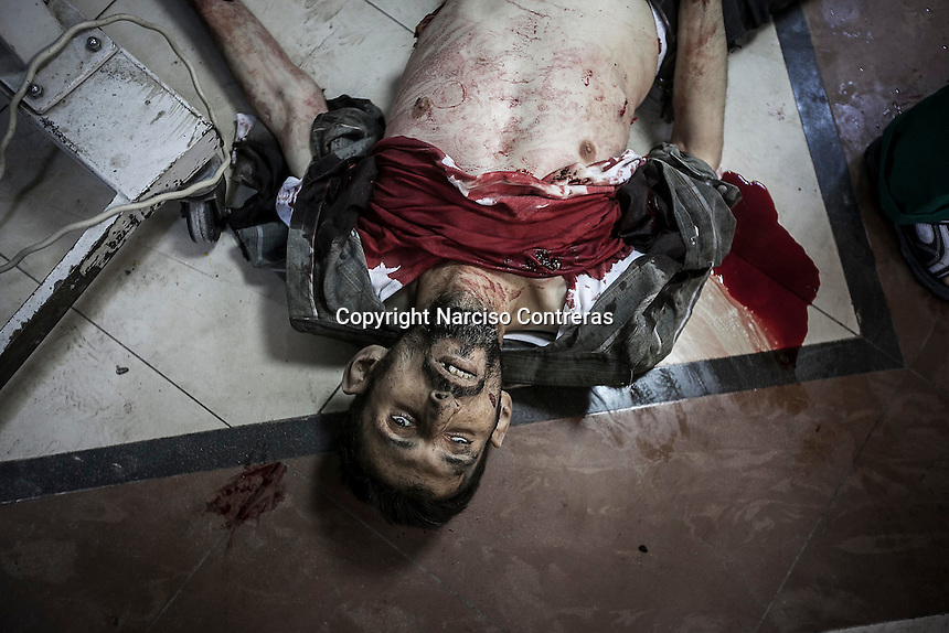In this Tuesday, Oct. 23, 2012 photo. A Syrian civilian's body lays down on the floor of a hospital in Tarik Al-Bab as he arrives killed by shrapnel after an attack by mortar shelling targeted one bakery in Hananu district, at the northeast of Aleppo City. (AP Photo/Narciso Contreras).