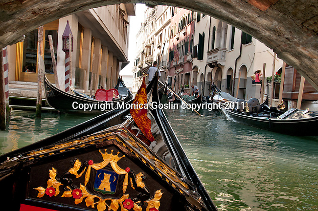 Riding a gondola down a canal and under a bridge in Venice, Italy