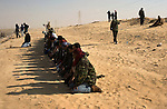 Opposition rebels pray in the afternoon near the city of Ajdabiya, Libya, March 24, 2011. Despite air strikes from Western war planes, which crippled Col. Muammar Qaddafi's military capability, the rebels seemed unable to advance and retake the city.