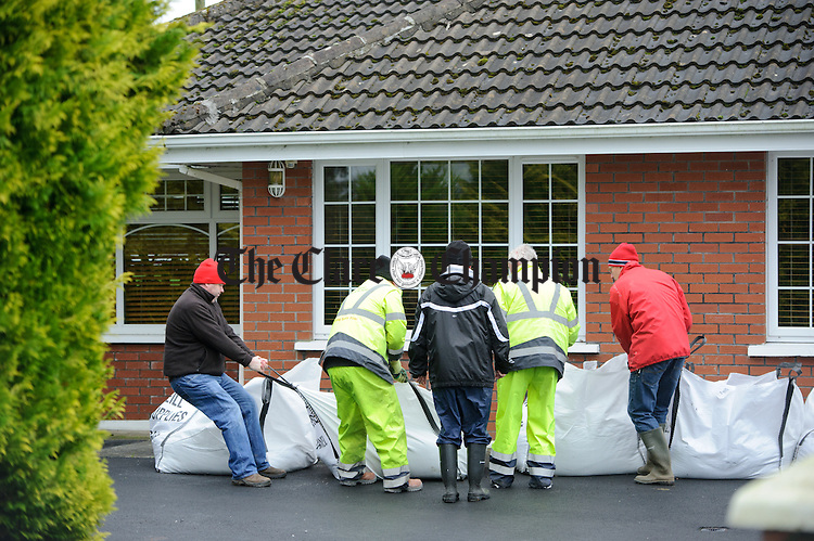 Clare County Council workers and locals line up sand bags around a house at Springfield, Clonlara as they prepare for flooding due to water being released at the Parteen Weir. Photograph by John Kelly.