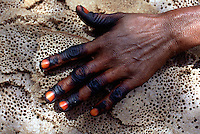 "Eritrea. Southern Debud Zone. Tseda. Small village in the country. A woman's hand with varnished nails and fingers painted in black on the local bread ""injera"".  © 2002 Didier Ruef"