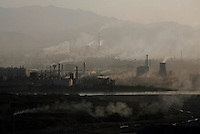 Factories and power stations lets out their smoke in a valley around dusk in northern Ningxia Hui Autonomous Region, China. According to the first-quarter report of the State Environmental Protection Administration (SEPA), pollution across the country has been worsening and foul air emissions are beyond acceptable limits. Pollution index in some cities is above 300. Worsening air and water pollution made cancer the top killer in China last year..18 May 2007