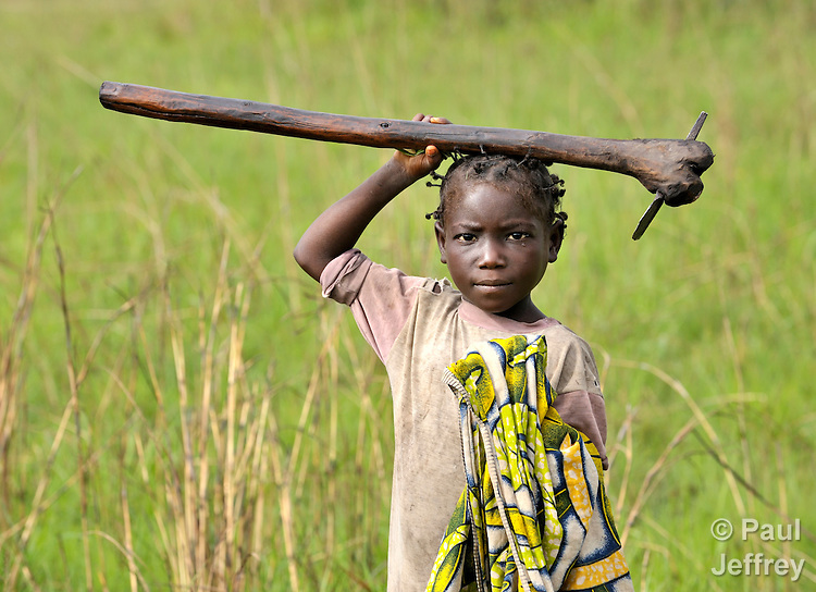 A girl walks home after working in her family's farm plot in the village of Lunge, near Kamina, in the Democratic Republic of the Congo.