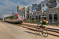 The Capital MetroRail train and a bicyclist ride along the Eastside Station Apartments, a mega apartment complex next to the Plaza Saltillo Capital MetroRail commuter rail station in East Austin, Texas.