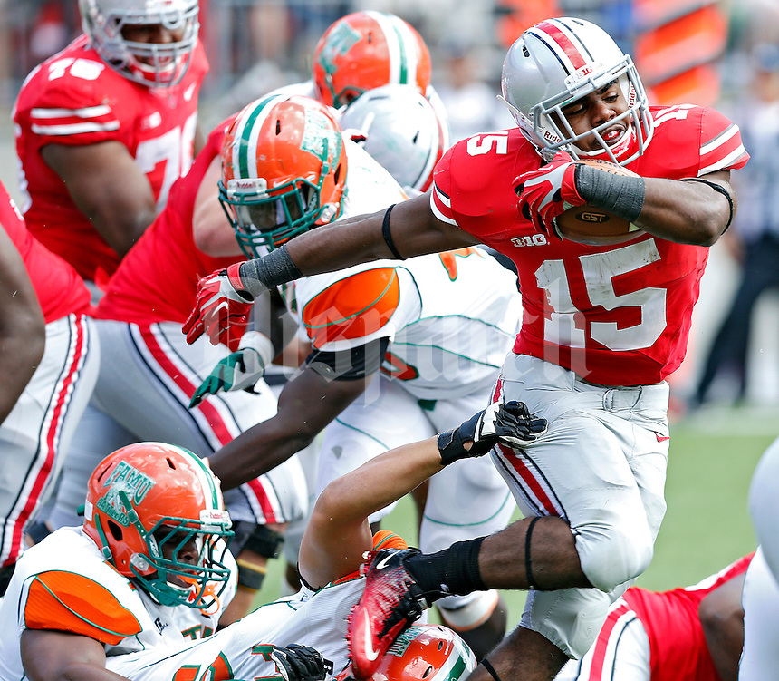 Ohio State Buckeyes running back Ezekiel Elliott (15) gets past the Florida A&M Rattlers defense in the 4th quarter during their college football game at Ohio Stadium on September 21, 2013.  (Dispatch photo by Kyle Robertson)