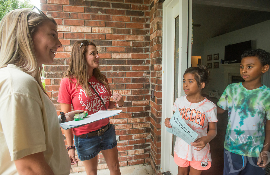 NWA Democrat-Gazette/BEN GOFF @NWABENGOFF<br /> Halston Shaw (from left), a 4th grade teacher at Tucker Elementary, and Kim White, the school's library media specialist, deliver an invitation to 4th grade students Arianna Mata and Magdiel Berroa at their home Wednesday, Aug. 8, 2018, in a neighborhood near the school in Rogers. Teachers and staff at the school split into groups to knock on the doors of the school's more than 600 students to personally invite their family to the meet and greet at the school Monday. Casey Wolfe, a kindergarten teacher at the school, helped organize the community walk after attending a Professional Learning Community seminar over the summer break. Wolfe hopes the effort will get more parents involved with the school.