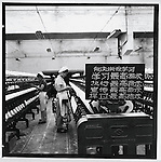 "In a textile mill in Jiamusi City, a placard reminds workers to ""Learn, carry out, propagandize, and protect Chairman Mao's supreme instruction. It is right to rebel."" Heilongjiang province, 25 July 1967."
