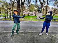 New York, New York City. 4/4/20. A couple of friends social distance while wearing the recommended face coverings in Central Park due to Coronavirus.