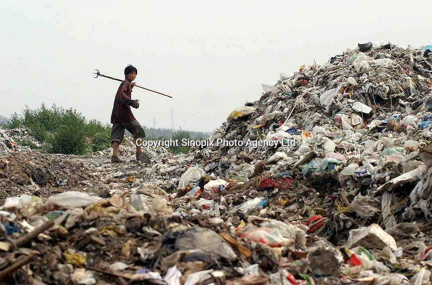 A garbage picker heads home after working in a garbage dump on the west side of Beijing. The pickers find things they can salvage and resell, or recycle for about 8 mao ($.10  Euro)..18-JUL-03