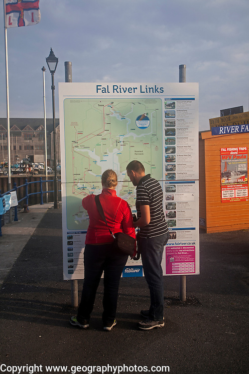 People looking at a map of River Fal transport links Prince of Wales pier, Falmouth, Cornwall, England, UK