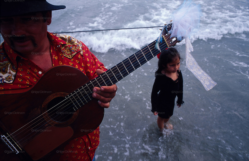 Europe, France, Camargue, Saintes Maries de la Mer, Gypsy Pilgrimmage 'Pelerinage des Gitans aux Saintes Maries de la Mer'. After the procession, a Gypsy plays guitar on the seashore. Gypsies from all over the world come to celebrate their patron Saint Sara who is carried by them from the church to the sea-shore. May 24th and 25th every year.