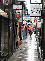 A Geisha with a red Japanese umbrella walks through the historic Pontocho district