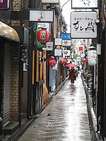 A Geisha with a red Japanese umbrella walks through the historic Pontocho district