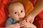 6 month old baby boy holding grandmother's hand closeup, looking apprehensive